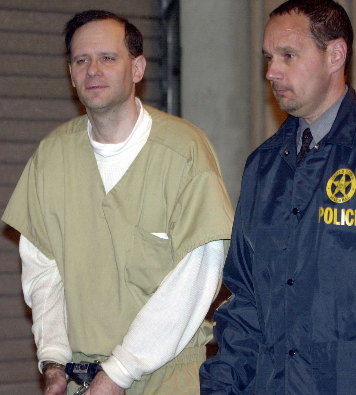 FILE - In this May 15, 2002 file photo, Martin Frankel, a financier accused of stealing more than $200 million from insurance companies, is escorted from U.S. District Court in New Haven, Conn. Frankel was sentenced in 2004 to 17 years behind bars, and released to a halfway house in September 2015. Frankel is due back in New Haven federal court Thursday, Oct. 1, 2015, less than a month after getting out of prison, charged with violating the terms of his release. (AP Photo/Bob Child, File)