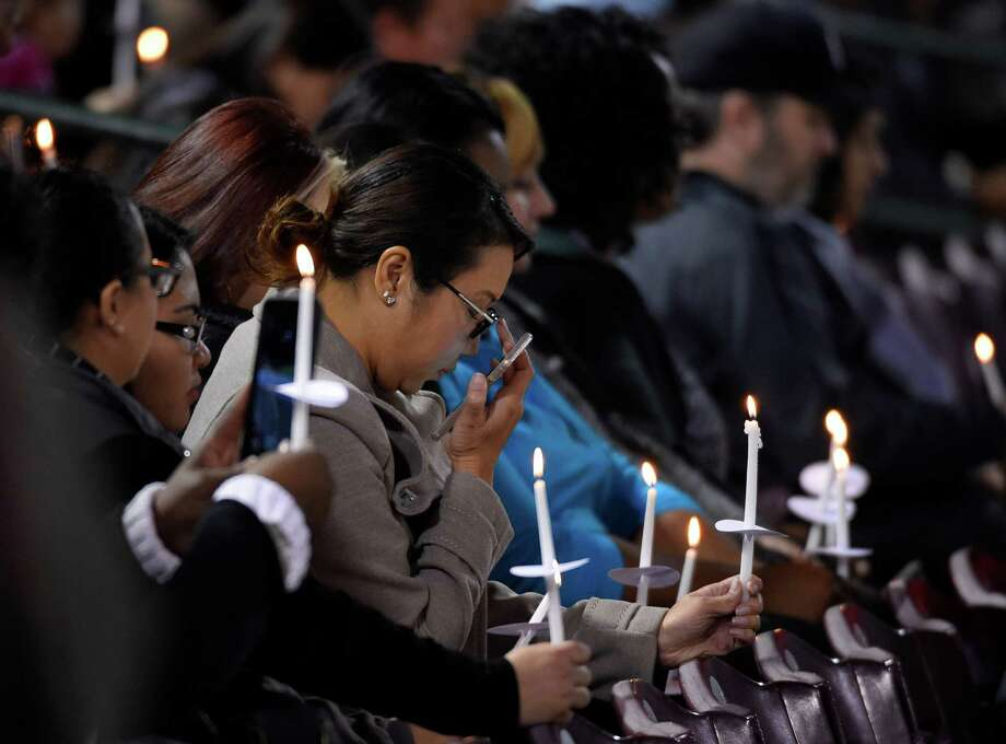 Mourners hold candles during a vigil at San Manuel Stadium, Thursday, Dec. 3, 2015, in San Bernardino, Calif for multiple victims of of a shooting that took place at a holiday banquet on Wednesday. A heavily armed man and woman opened fire killing multiple people and seriously wounding others in a precision assault, authorities said. Hours later, they died in a shootout with police. (AP Photo/Mark J. Terrill) Photo: Mark J. Terrill, STF / Associated Press / AP
