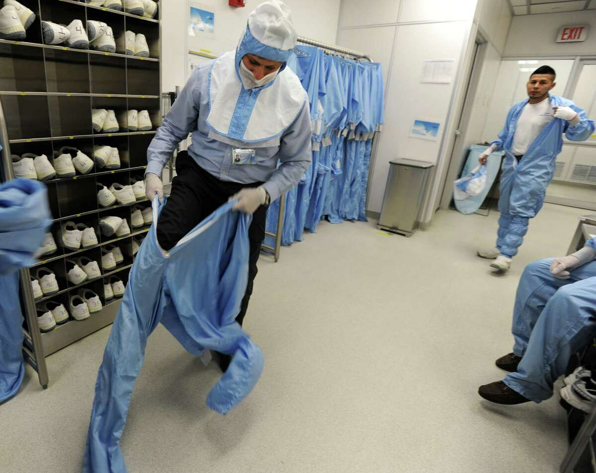 Victor Crudo, director of manufacturing operations, suits up before entering a clean room where semiconductor equipment is made at the ASML manufacturing plant in Wilton, Conn.