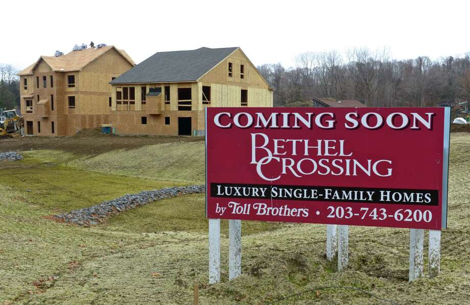 A sign at the intersection of Plumtrees Road, Maple Avenue and Maple Avenue Ext, for Bethel Crossing, the latest Toll Brothers housing development in the area, a complex of single family homes. Tuesday, December 1, 2015, in Bethel, Conn. Photo: H John Voorhees III / Hearst Connecticut Media / The News-Times