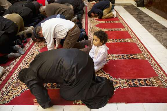 Aiden Abdelaziz, 2, attends prayers with his father, Mohamed Abdelaziz, 22, originally from Cairo, Egypt, left, as Rep. Don Beyer, D-Va., and other local elected officials attended Friday prayers at Dar al-Hijrah Mosque in Falls Church, Va., Friday, Dec. 4, 2015. Beyer and other elected officials attended prayer services at the northern Virginia mosque as a show of solidarity with the region's Muslim population. (AP Photo/Jacquelyn Martin)