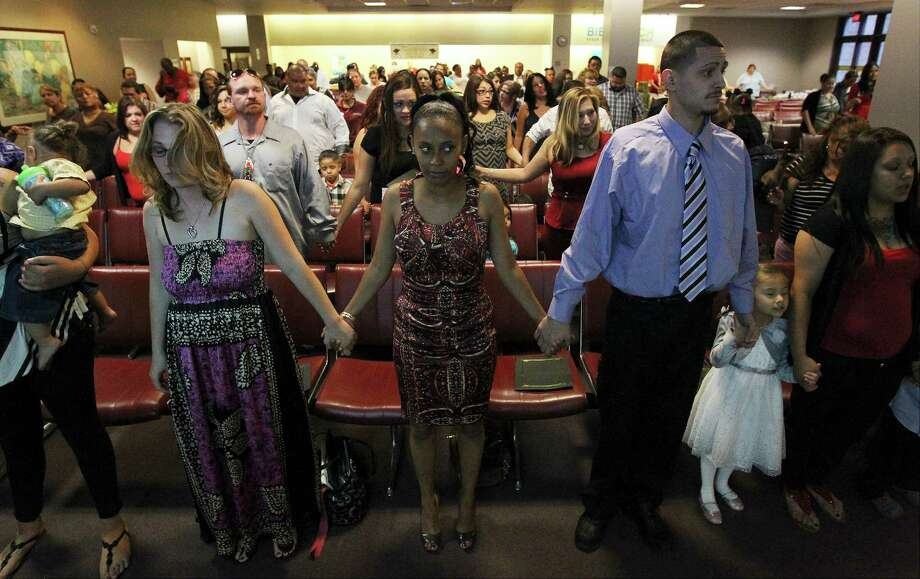 """Bexar County Family Drug Treatment Court graduates hold hands in reciting the program oath at the conclusion of ceremonies on Friday, May 2, 2014. Since 2004, the court has graduated 231 people who have received treatment for their addiction instead of incarceration. Judge Peter Sakai who oversees the court believes the approach works. """"When we can end the cycle of drug abuse, domestic abuse and child neglect at the parents' level, then we have given their children a better chance at never entering the cycle in their own lives,"""" Sakai said. (Kin Man Hui/San Antonio Express-News) Photo: Kin Man Hui, Staff / San Antonio Express-News / ©2014 San Antonio Express-News"""