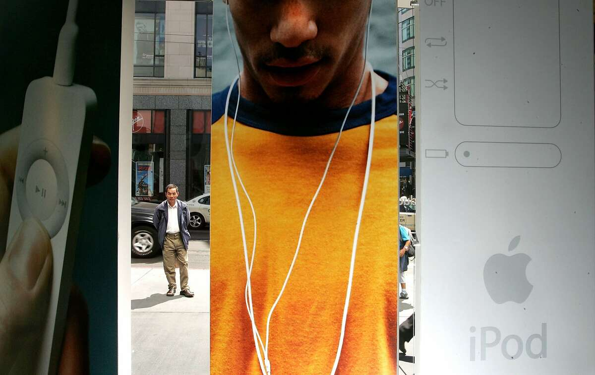 Once cool: A man looks at a window 2005 advertising display for the iPod Shuffle at the Apple Store in San Francisco. Wear it today? Not cool.