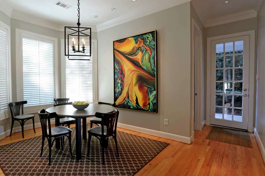 Just off the kitchen, the Hightowers' breakfast nook is open and bright. Spare furniture and simple lines give the couple's oversize Mary Quiros painting center stage. Photo: Gary Coronado, Staff / © 2015 Houston Chronicle