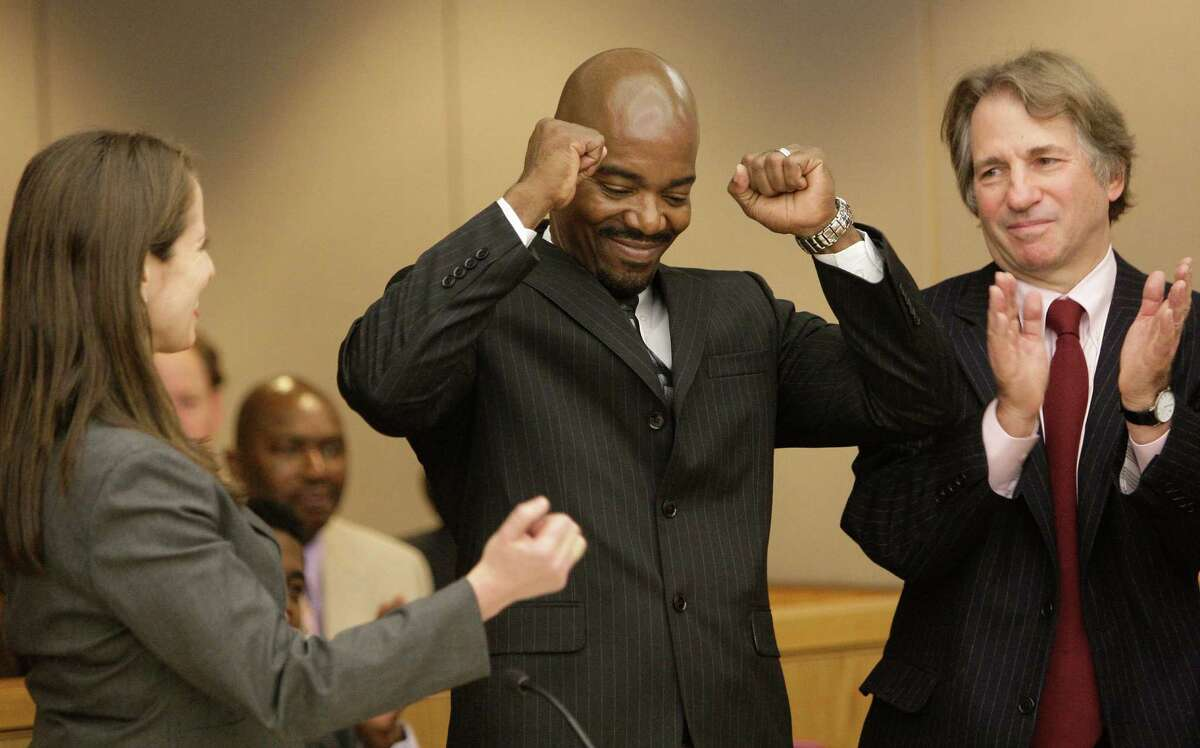 Cornelius Dupree Jr., center, raises his hands in celebration with his lawyer Nina Morrison, left, and attorney Barry Scheck in Dallas on Jan. 4, 2011. Dupree served 30 years for rape and robbery before being exonerated by DNA evidence.