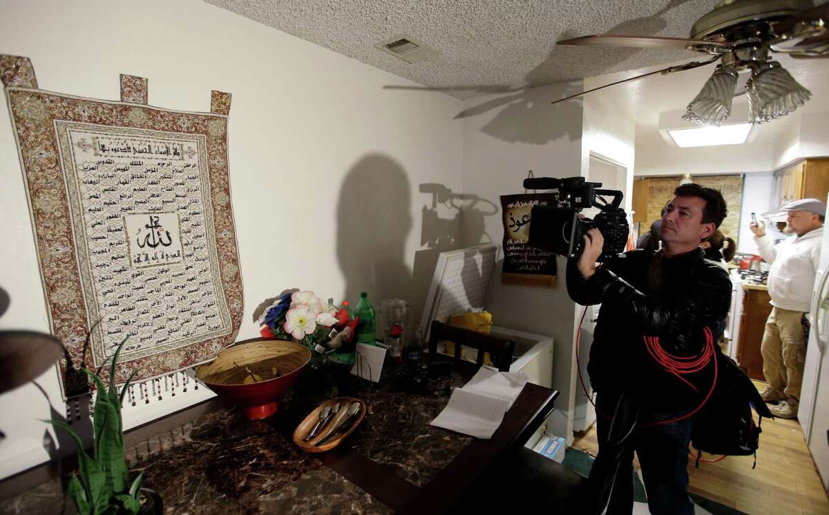 A member of the media films a wall tapestry displaying religous writing in the living room of an apartment in Redlands, Calif., shared by San Bernardino shooting rampage suspects Syed Farook and his wife, Tashfeen Malik, Friday, Dec. 4, 2015, after the building landlord invited media into the townhouse rented by the California attackers.