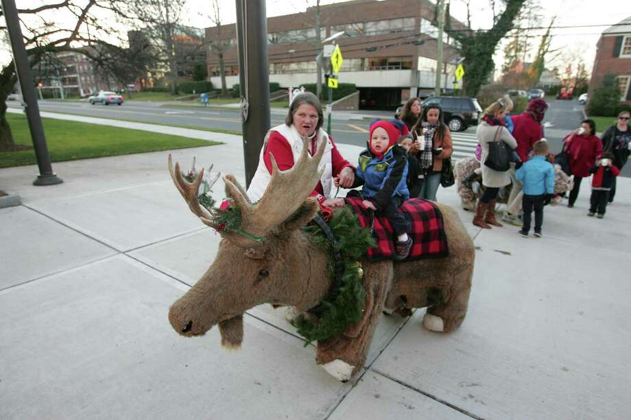 Cherri Meyer of Wallingford, Conn. gives Greyson Lowthert, 2 of Greenwich, a ride on a mechanical holiday moose as he waits for the annual lighting of the Holiday tree in front of Greenwich Town Hall in Greenwich, Conn. on Dec. 4, 2015. Photo: Matthew Brown / For Hearst Connecticut Media / Connecticut Post Freelance