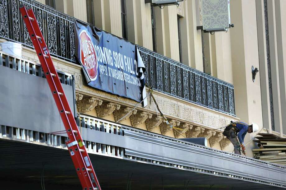 A construction worker works on the sidewalk cover at Rivercenter mall's historic Joske's building. Photo: Bob Owen /San Antonio Express-News / San Antonio Express-News