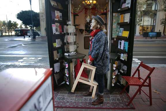 Courtney Riddle, owner of the Grand Newsstand, sets up chairs as she opens The Grand Newsstand for business  on  Friday, December 4,  2015 in San Francisco, Calif.