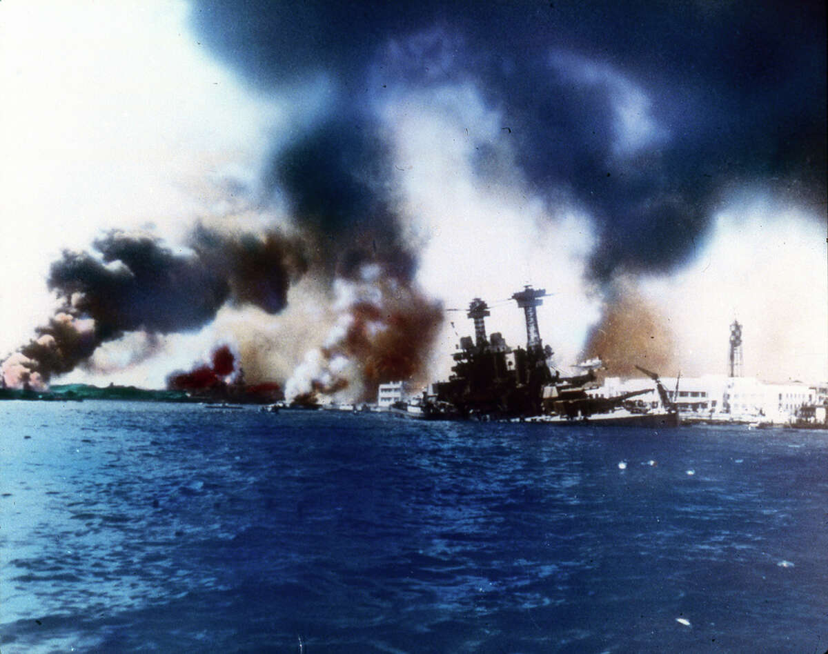 The battleship USS California sinks near Ford Island after the Japanese bombed and torpedoed the ship during the attack on Pearl Harbor, Honolulu, Oahu, Hawaii, December 7, 1941. The destroyer USS Shaw burns in the far left.
