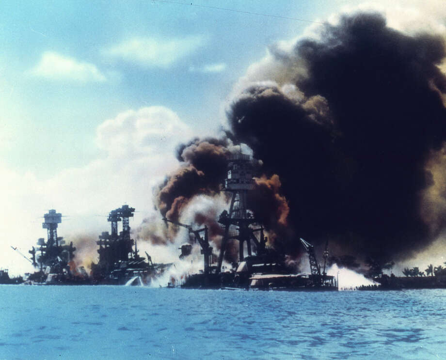 View of battleship row as explosions damage three American battleships during the Japanese attack on Pearl Harbor, Honolulu, Oahu, Hawaii, December 7, 1941. From left to right, the USS West Virginia, the USS Tennessee, and the USS Arizona. Photo: Interim Archives, Getty Images / Archive Photos