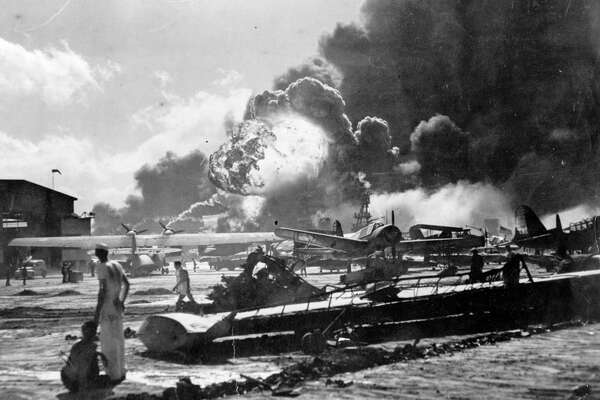 An explosion at the Naval Air Station, Ford Island, Pearl Harbour (Pearl Harbor) during the Japanese attack. Sailors stand amid wrecked watching as the USS Shaw explodes in the center background. The USS Nevada is also visible in the middle background, with her bow headed toward the left.