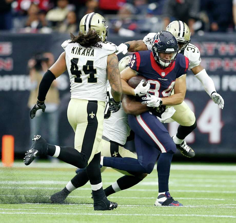 Texans tight end Ryan Griffin hangs onto the ball after catching a pass as New Orleans Saints free safety Jairus Byrd (31) and cornerback Delvin Breaux (40) tackle him in the third quarter. Photo: Karen Warren, Staff / © 2015  Houston Chronicle