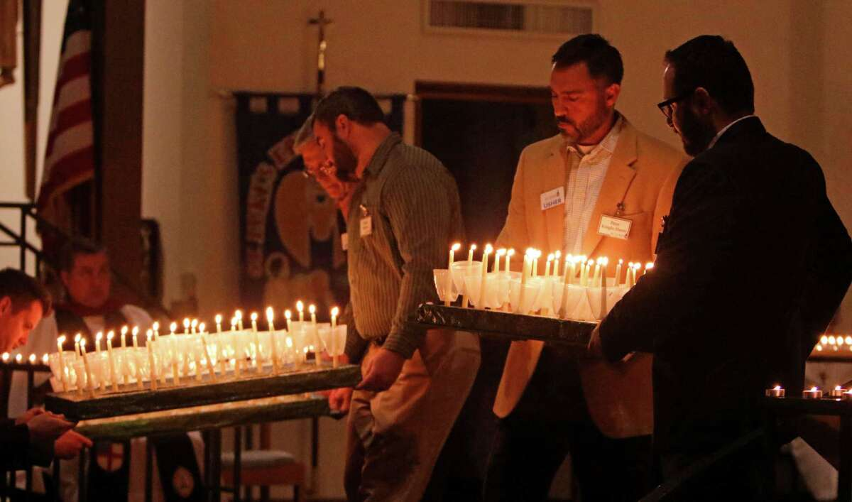 Ushers bring in candles to be distributed to the congregation at the St. Luke's Episcopal Church Advent Lessons and Carols Service on Nov. 29, days after the parish school notified parents it would accept and embrace a transgender student.