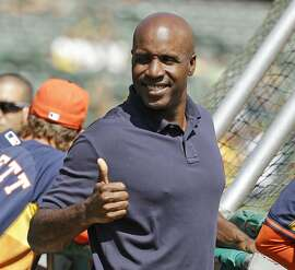 FILE - In this Sept. 6, 2014, file photo, career home run leader Barry Bonds gives a thumbs up while standing behind the batting cage and watching the Houston Astros take batting practice before the start of their baseball game against the Oakland Athletics, in Oakland, Calif. Steroids-tainted home run king Barry Bonds is returning to baseball full time as hitting coach for the Miami Marlins. (AP Photo/Eric Risberg, File)