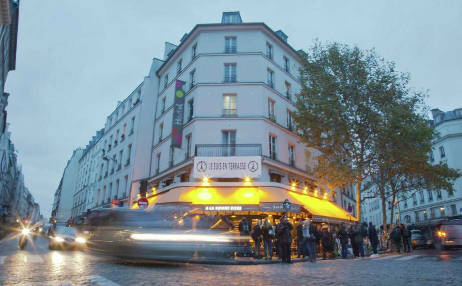 Cars pass by and people gather around La Bonne Biere cafe in Paris during its reopening Friday, Dec. 4, 2015. The cafe where five people were killed by a squad of Islamic extremist gunmen on Nov. 13, terrorizing central Paris reopened for business Friday. (AP Photo/Jacques Brinon) Photo: Jacques Brinon, STF / AP