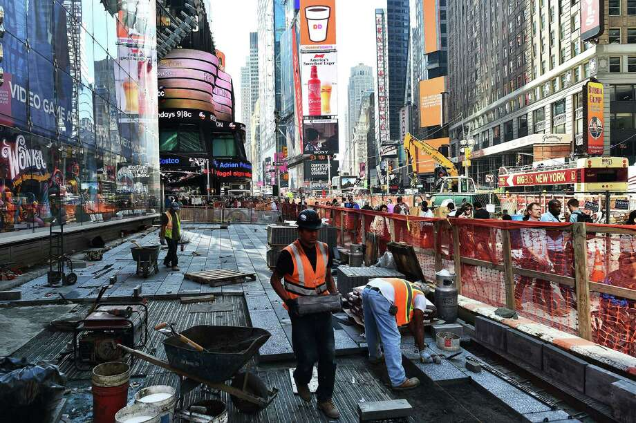 Laborers work on a footpath and roadway construction site in Times Square in New York. The U.S. economy pumped out 211,000 new jobs in November, the Labor Department said. Photo: Jewel Samad /AFP / Getty Images / AFP
