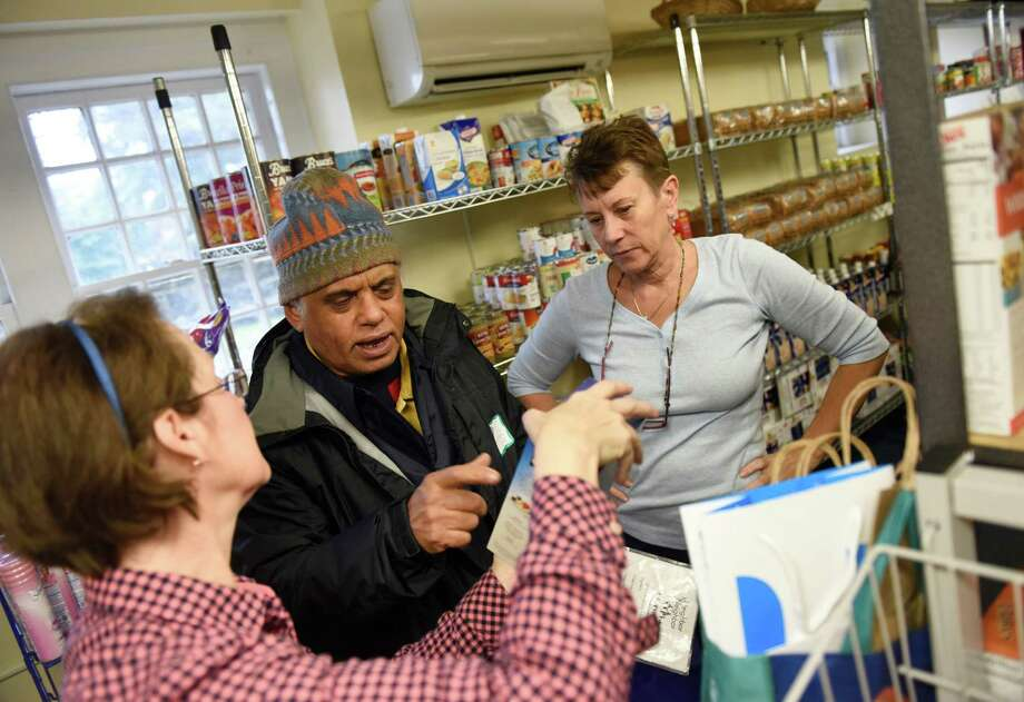 Volunteers Molly Tanaka, left, and Marie Wardell assist customer Richard Germain, of Greenwich, in picking out food items at the food pantry at Neighbor to Neighbor in Greenwich, Conn. Wednesday, Dec. 2, 2015.  Neighbor to Neighbor provides donated food and clothing to low-income residents of Greenwich by using a points system to give a similar experience to shopping at a grocery store or department store. Photo: Tyler Sizemore / Hearst Connecticut Media / Greenwich Time
