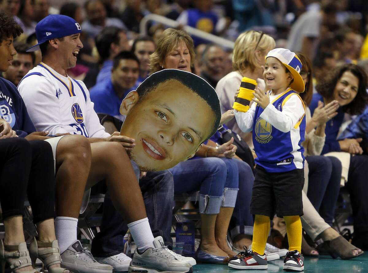 A Golden State Warriors' fan enjoys getting a t-shirt during 4th quarter of Warriors' 95-87 win over Toronto Raptors during NBA preseason game at SAP Center in San Jose, Calif., on Sunday, October 5, 2015.