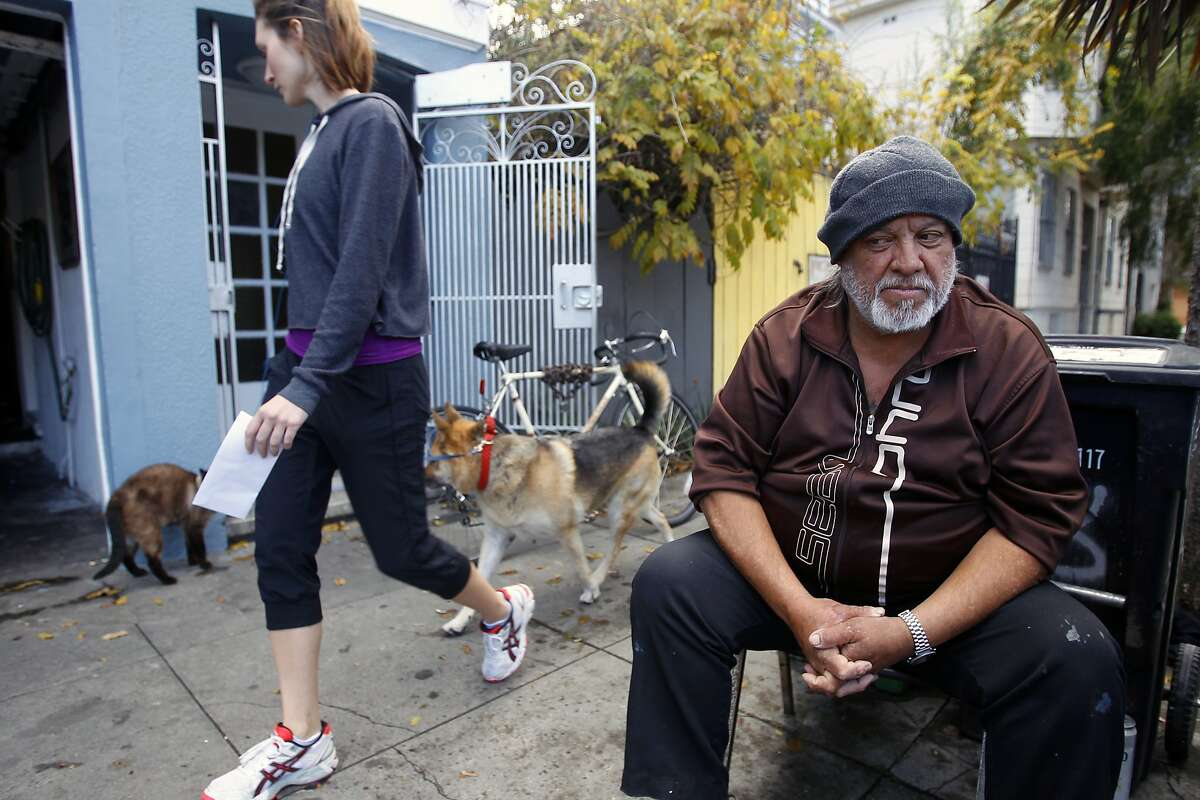 Serafin Saavedra, who has lived on 23rd. St. between Harrison and Alabama streets since 1978, sits in front of his family's house as Allisha Self passes on her way to send a piece of mail with her dog Zoe.
