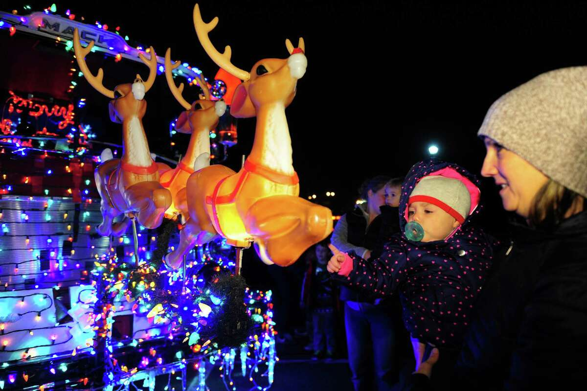 Mimi Voccola, 1, reaches out to touch Rudolph attached to the front of a Trumbull fire truck during the City of Trumbull's annual Christmas Tree Lighting at the Town Hall Gazebo in Trumbull, Conn. on Friday Dec. 4, 2015. While waiting for the trees to be lit, residents were treated to Christmas songs performed by the Madison Middle School's band. To cap off the celebration, Santa Claus arrived on the fire truck which was decorated with thousands of Christmas lights. After arriving Santa greeted kids and gave out candy canes.