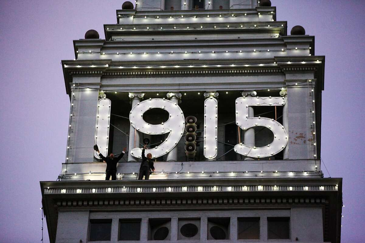Jim Phelan (left) and his nephew Tyrone Mancuso stand on the ledge of the Ferry building as part of the final lighting ceremony of the 1915 lights at the Ferry building in San Francisco, California on Friday, December 4, 2015.