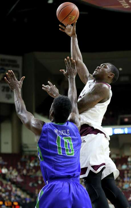 Texas A&M's Jalen Jones (12) makes a basket against Florida Gulf Coast University's Kevin Mickle (10) during an NCAA college basketball game in College Station, Texas, Wednesday, Dec. 2, 2015. (AP Photo/Sam Craft) Photo: Sam Craft, STR / AP