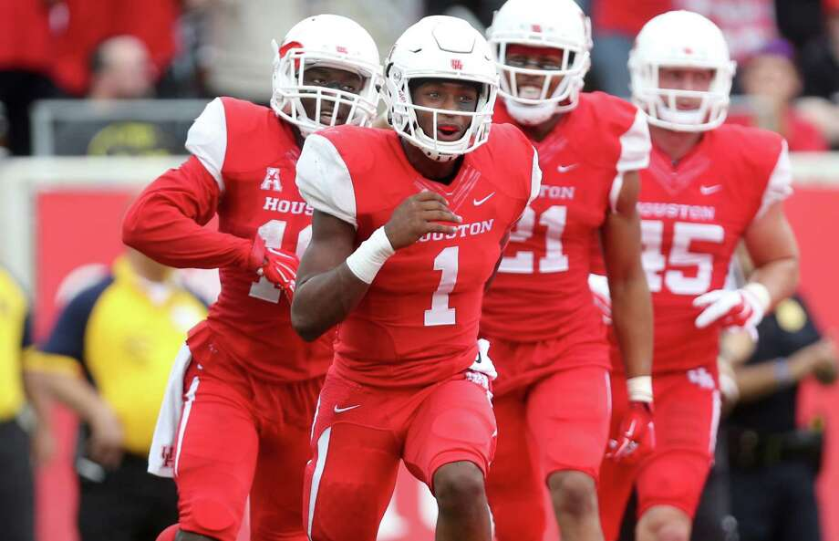 Houston Cougars quarterback Greg Ward Jr. (1) is congratulated by teammates after scoring a second-quarter touchdown against the Navy Midshipmen at TDECU Stadium on Nov. 27, 2015, in Houston. Photo: Gary Coronado /Houston Chronicle / © 2015 Houston Chronicle