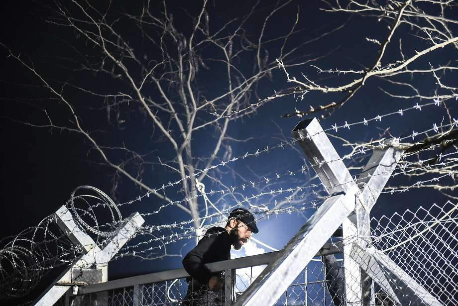 A migrant stands on a border gate as he and other migrants and refugees try to cross the Greek-Macedonian border near the village of Idomeni, Greece, on December 3, 2015.