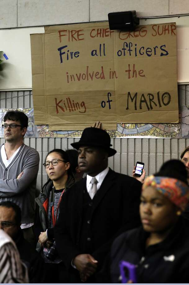 Several signs reflect the feelings of the crowd as the San Francisco Police department hosts a town hall meeting, on Fri. December 4, 2015 to discuss the officer-involved shooting of 26-year-old Mario Woods in the Bayview neighborhood that sparked outrage nationwide after a video taken of the shooting was circulated on social media, in San Francisco, Calif. Photo: Michael Macor, The Chronicle