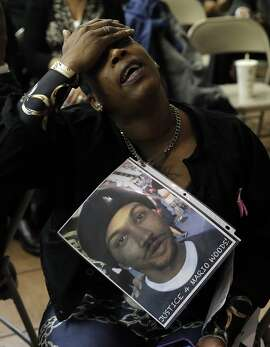 A woman who declined to give her name displayed a photo of the victim Mario Woods as the San Francisco Police department hosted a town hall meeting, on Fri. December 4, 2015 to discuss the officer-involved shooting of 26-year-old Mario Woods in the Bayview neighborhood that sparked outrage nationwide after a video taken of the shooting was circulated on social media, in San Francisco, Calif.