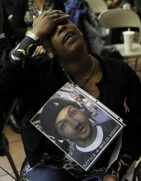 A woman who declined to give her name displayed a photo of the victim, Mario Woods, during a town hall meeting on Dec. 4. Photo: Michael Macor, The Chronicle