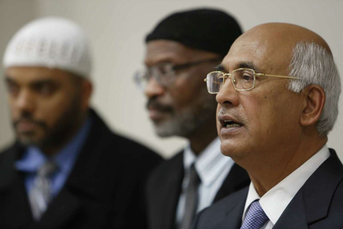 MJ Khan, right, and Iman Wazir Ali (left-right, background) Mustafa Carroll held a press conference to condemn San Bernardino shooting at the Islamic Society of Greater Houston Friday, Dec. 4, 2015, in Houston.