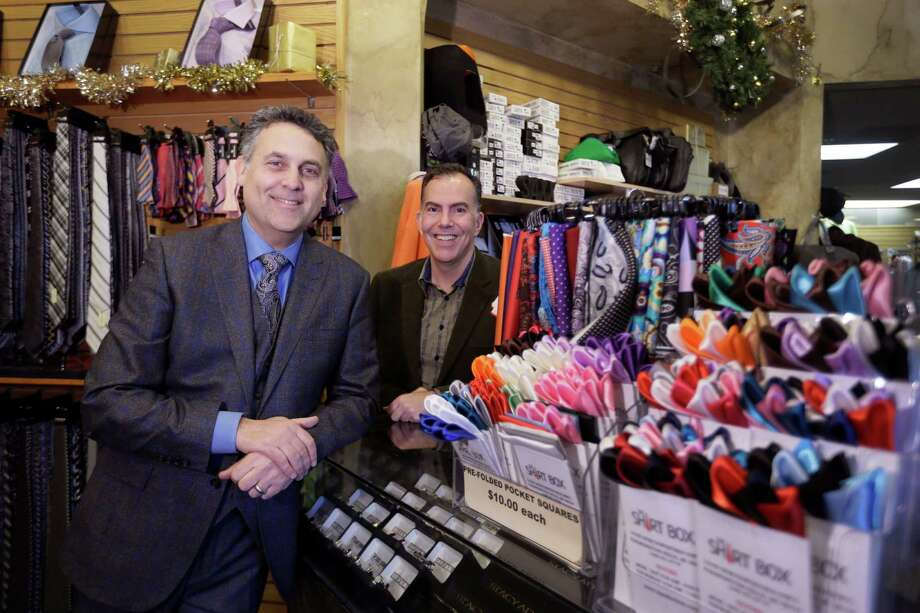 Rod Brown, left, and Ron Elkus own The Shirt Box in Farmington Hills, Mich. They hold events like bourbon tastings to draw customers in the lull between Thanksgiving weekend and the last 10 days of the holiday shopping season. Photo: Carlos Osorio, STF / AP