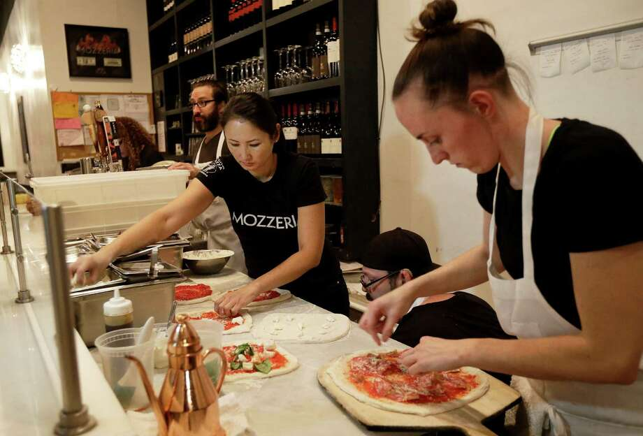 In this Nov. 5, 2015 photo, Mozzeria owner Melody Stein, left, and Sabrina Ferguson makes pizzas at the restaurant in San Francisco. Mozzeria owners Russ and Melody Stein as well as staff workers are deaf. (AP Photo/Jeff Chiu) Photo: Jeff Chiu, STF / AP