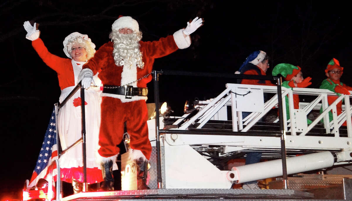 Santa and Mrs. Claus, aboard a fire truck, greet hundreds gathered on Town Hall Green for the lighting of the town's Christmas tree.