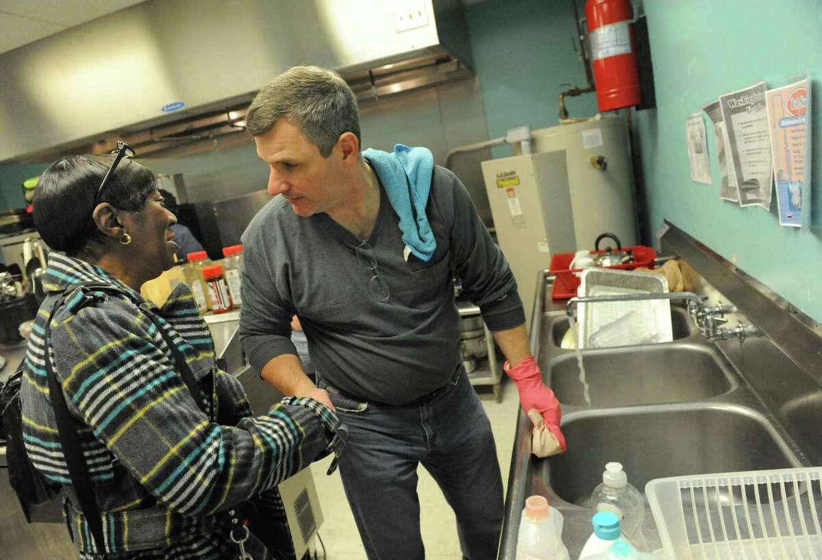 Albany Police Chief Brendan Cox takes a break from washing dishes to talk with fire victim Helen Holmes during a Dominican and soul food dinner to benefit the victims of the South End fires and their families at Reigning Life Family Church on Saturday Dec. 5, 2015 in Albany, N.Y. The event was organized by AVillage...Inc., the church and the Alcantara family and friends. (Michael P. Farrell/Times Union)