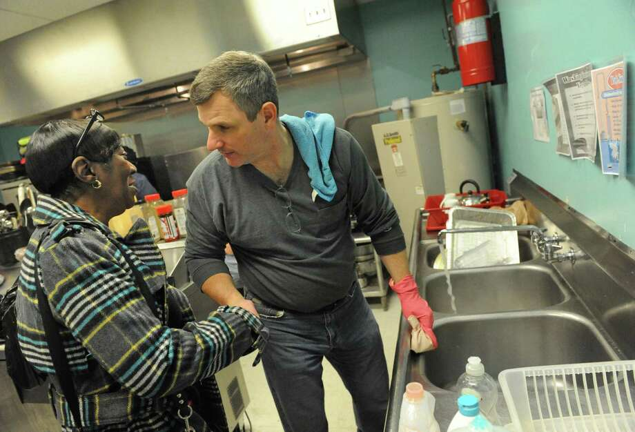 Albany Police Chief Brendan Cox takes a break from washing dishes to talk with fire victim Helen Holmes during a Dominican and soul food dinner to benefit the victims of the South End fires and their families at Reigning Life Family Church on Saturday Dec. 5, 2015 in Albany, N.Y. The event was organized by AVillage...Inc., the church and the Alcantara family and friends. (Michael P. Farrell/Times Union) Photo: Michael P. Farrell / 10034517A