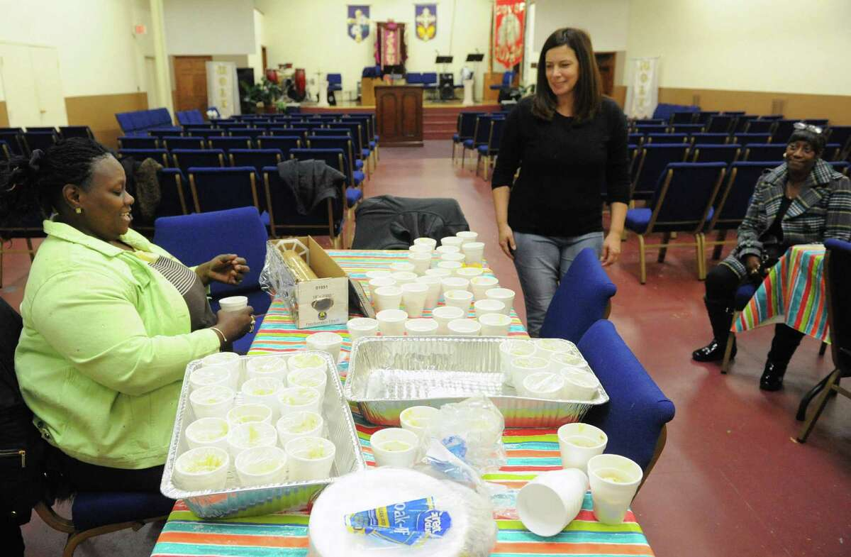 Fire victims Lynette Moses, left, and Helen Holmes, right, are joined by volunteer Heidi Hicks during a Dominican and soul food dinner to benefit the victims of the South End fires and their families at Reigning Life Family Church on Saturday Dec. 5, 2015 in Albany, N.Y. The event was organized by AVillage...Inc., the church and the Alcantara family and friends. (Michael P. Farrell/Times Union)