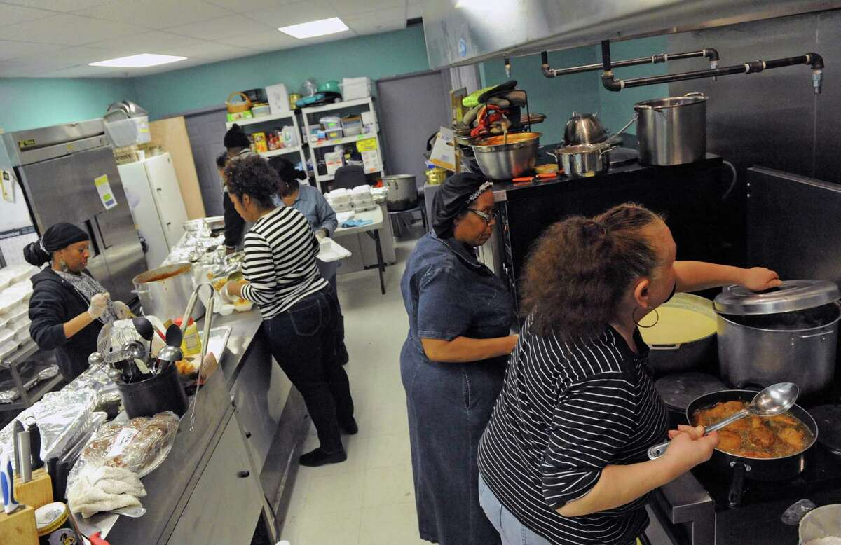 Volunteers work at preparing a Dominican and soul food dinner to benefit the victims of the South End fires and their families at Reigning Life Family Church on Saturday Dec. 5, 2015 in Albany, N.Y. The event was organized by AVillage...Inc., the church and the Alcantara family and friends. (Michael P. Farrell/Times Union)