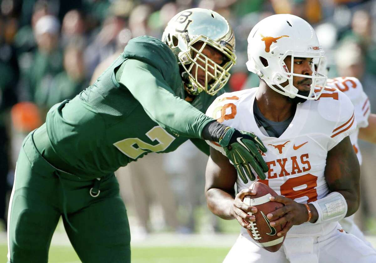 WACO, TX - DECEMBER 5: Tyrone Swoopes #18 of the Texas Longhorns eludes Shawn Oakman #2 of the Baylor Bears in the first quarter at McLane Stadium on December 5, 2015 in Waco, Texas.