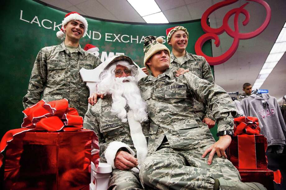 Nicolas Bush jumped on Santa's lap during a group picture at a holiday shopping event at Joint Base San Antonio-Lackland. Around 2,800 recruits took part, arriving in waves of 700 and given 90 minutes to find gifts. Photo: Photos By Julysa Sosa /For The San Antonio Express-News