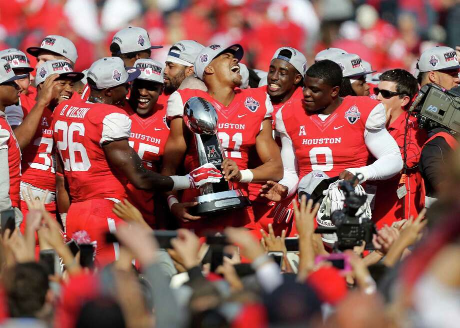 Houston Cougars wide receiver Chance Allen (21), shown with the American Athletic Conference Champion trophy, celebrates with teammates after the Cougars defeated the Temple Owls 24-13 in the inaugural game played at TDECU Stadium Saturday, Dec. 5, 2015, in Houston, Texas. Photo: Gary Coronado, Houston Chronicle / © 2015 Houston Chronicle
