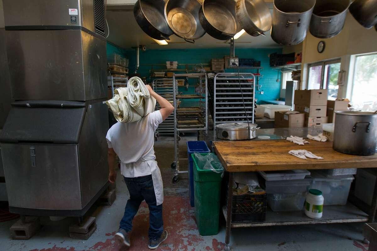 Jose Antonio Cen, a baker at La Victoria bakery, heads towards the kitchen area, Saturday, Dec. 5, 2015, in San Francisco, Calif.