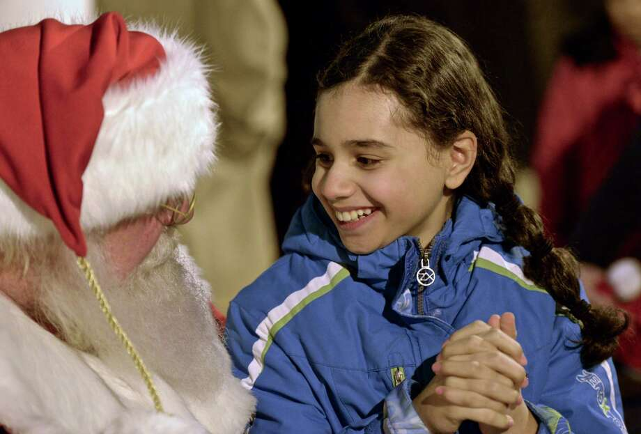 """Shazada Martinez, age 10, of Danbury, sits on Santa's lap and tells him what she wants for Christmas during the """"Light the Lights"""" holiday celebration in Danbury, Conn, on Saturday night, December 5, 2015. Photo: H John Voorhees III / Hearst Connecticut Media / The News-Times"""