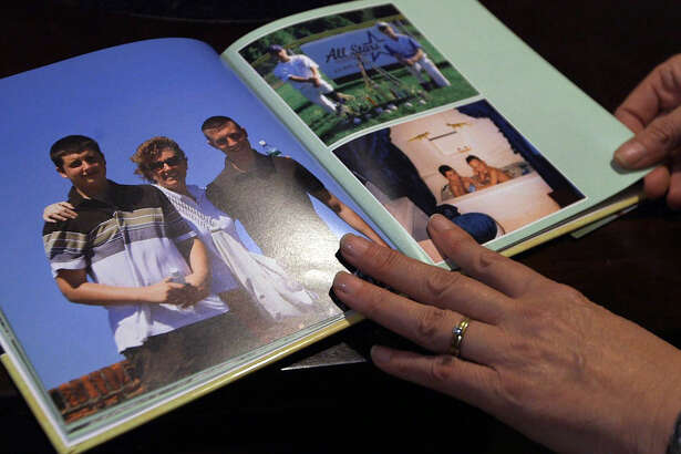 Kim Murdick, of West Sand Lake, looks through a memorial book of photographs that shows her son, Sean, left, and his brother, Tim Jr., in happier times before Sean died at 22 of a fatal heroin in a Florida treatment program on Sept. 28. (Photo by Nicole Van Slyke and Brian Flynn / WMHT)