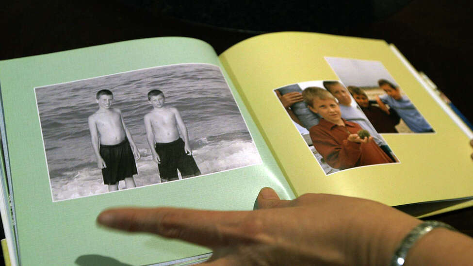Kim Murdick, of West Sand Lake, looks through a memorial book of photographs that shows her sons, Sean, left, and Tim Jr. in happier times before Sean died at 22 of a fatal heroin in a Florida treatment program on Sept. 28. (Photo by Nicole Van Slyke and Brian Flynn / WMHT)