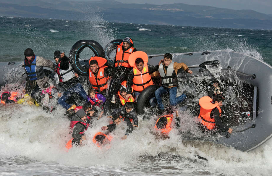 A boatload of refugees capsizes as it lands in rough seas on the island of Lesbos. Dozens of rafts and boats make the journey daily over the Aegean Sea, carrying desperate refugees fleeing war zones. Photo: Paula Bronstein / Special To The Chronicle / ONLINE_YES