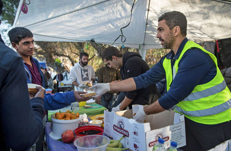 Alex Scotta, a San Francisco chef and caterer, hands out cheese sandwiches as he volunteers on Lesbos. Photo: Paula Bronstein / Special To The Chronicle / ONLINE_YES
