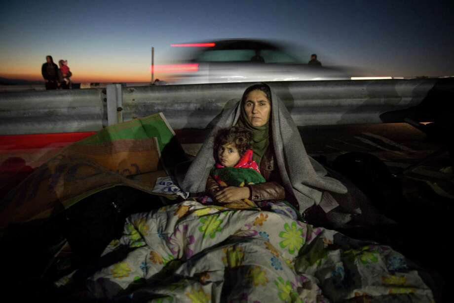 A Iraqi mother holds her daughter trying to keep warm at Oxy transitional camp on the island of Lesbos. Photo: Paula Bronstein / Special To The Chronicle / ONLINE_YES